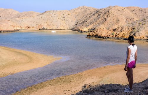 A tourist lady looking at a scenic fjord-like during low tide in Bandar Khairan, Sultanate of Oman