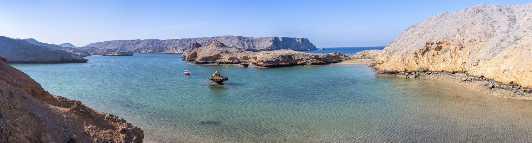 Panoramic view of the wild Coast of Bandar Khairan with clear water of the ocean and the arid mountains, Sultanate of Oman