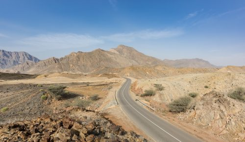 A road going thru the deserted mountains of the Sultanate of Oman