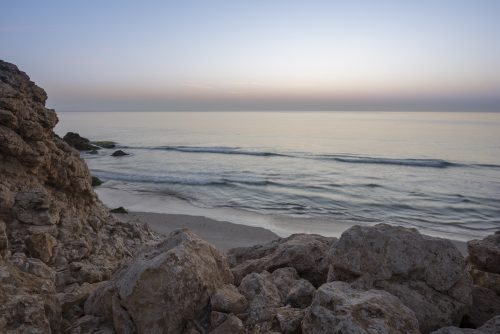 Sunrise over cliffs and sea of Oman (Gulf of Oman) wild coast of Ras Al Jinz, Sultanate of Oman