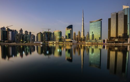 Dubai Downtown just before sunset with the buildings reflecting in the water canal. Dubai, United Arab Emirates, Middle East, Arabian Peninsula