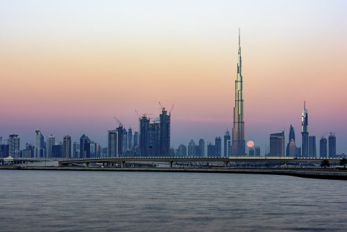 Moon passing behind the iconic Burj Khalifa at sunset. The light started to enlightened the top of the tower., United Arab Emirates, Middle East, Arabian Peninsula